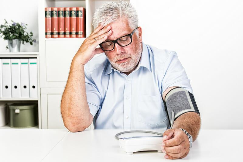 Bluthochdruck: Mann prüft seinen Blutdruck