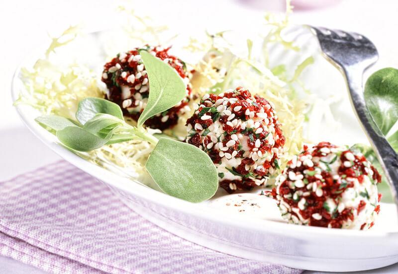 Frischkäse-Cranberries-Kügelchen auf frischem Salat