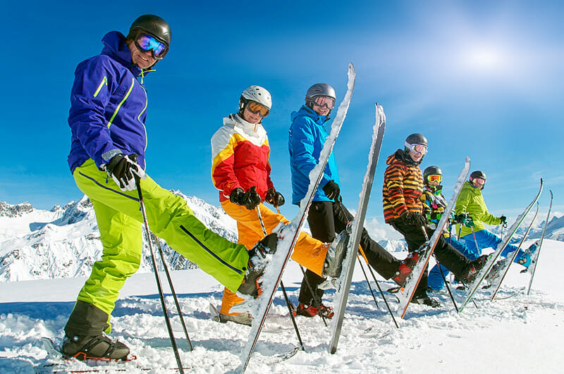 Richtiges Stretching auf der Piste - Gruppe Skifahrer in der Reihe