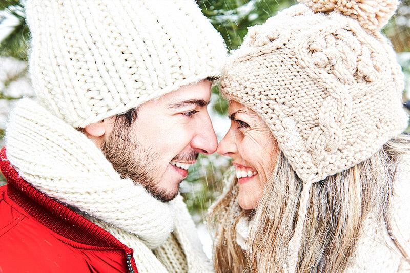 Glückliches Paar im Schnee zu Weihnachten