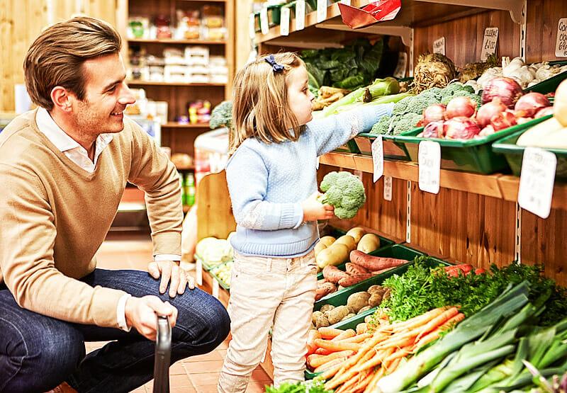Vater und Tochter kaufen frisches Gemüse