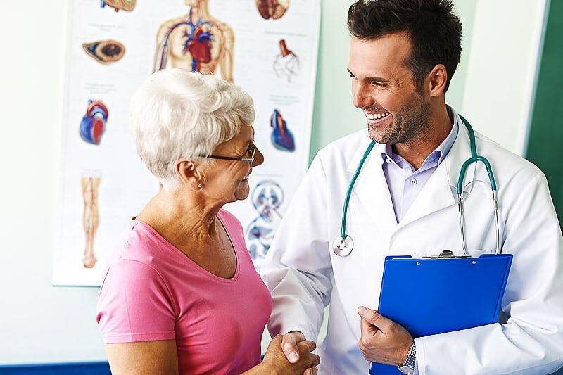 Freundlicher Arzt im Gespräch mit einer Patientin
